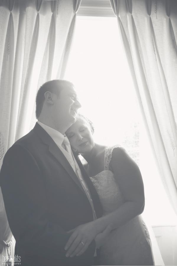 403_DSC_0199bw_bride_groom_photoshoot_window_light_posing_kiss_wedding_photography_photographer