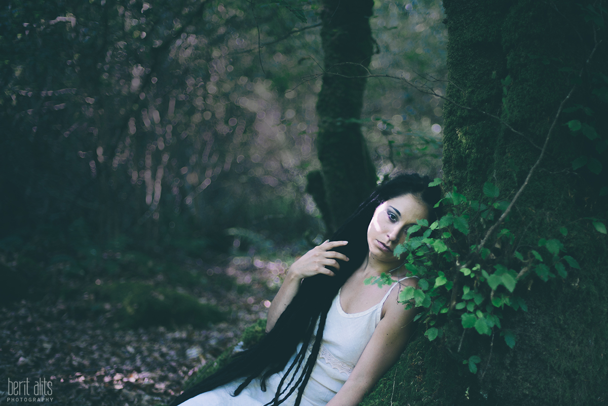 Girl with dreadlocks sitting under a tree