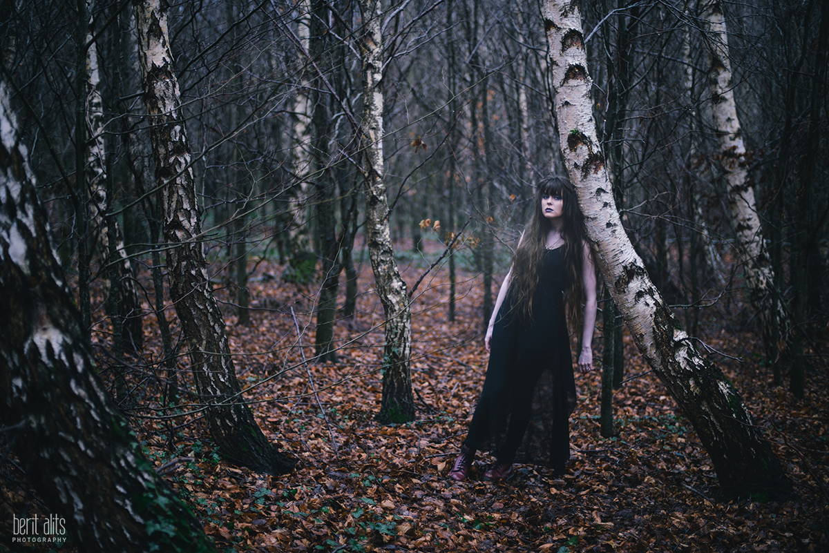 Girl standing in winter forest bare trees around her