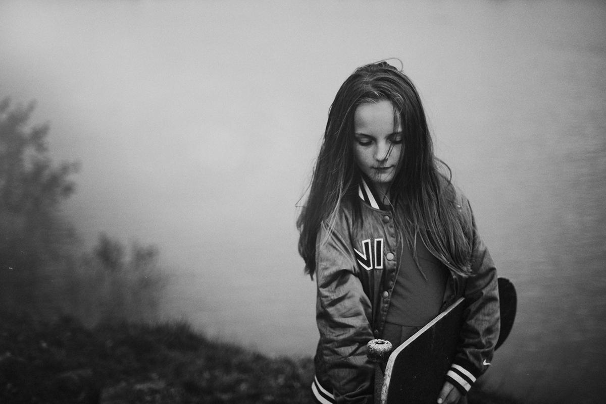 Girl with skateboard standing beside lake