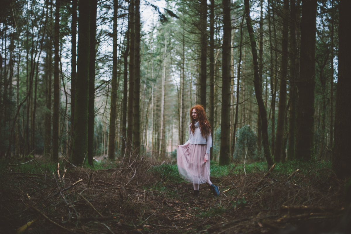 00 redhead girl standing in green pine tree forest