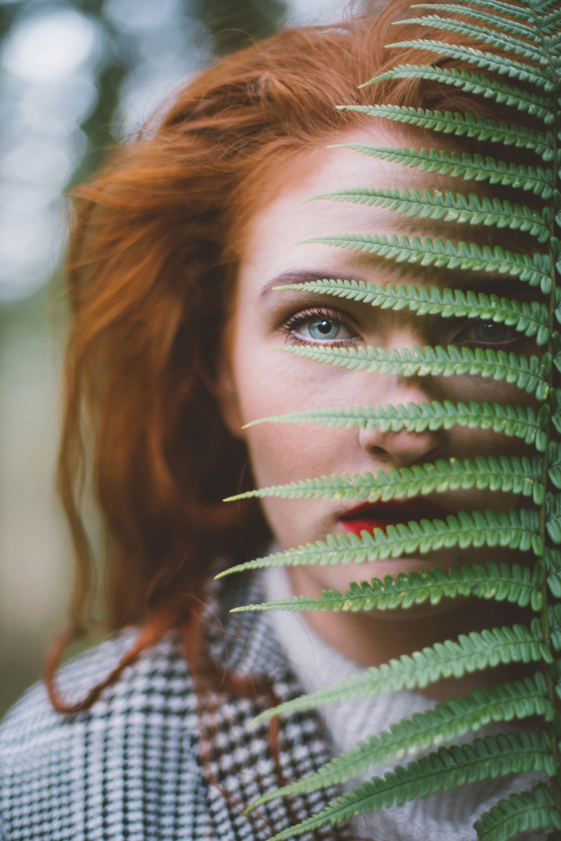 01 close up portrat of a girl with red hair and red lipstick holding a fern